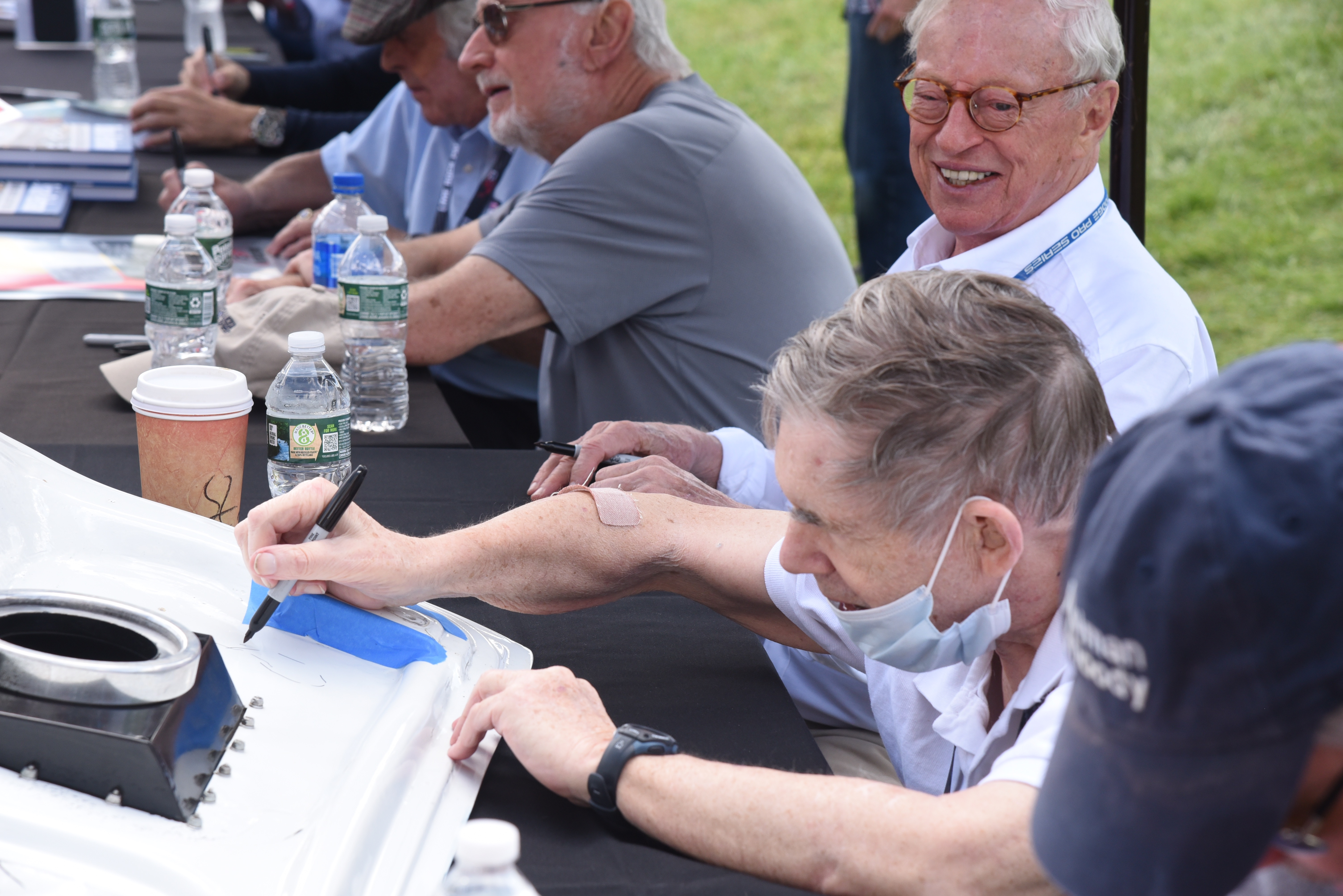 <strong>There were book signing events throughout the weekend, with authors including local race heroes Skip Barber (an owner of the track) and Sam Posey, who signed a car part for one enthusiastic fan.<em>Photoby Lans Christensen</em></strong>