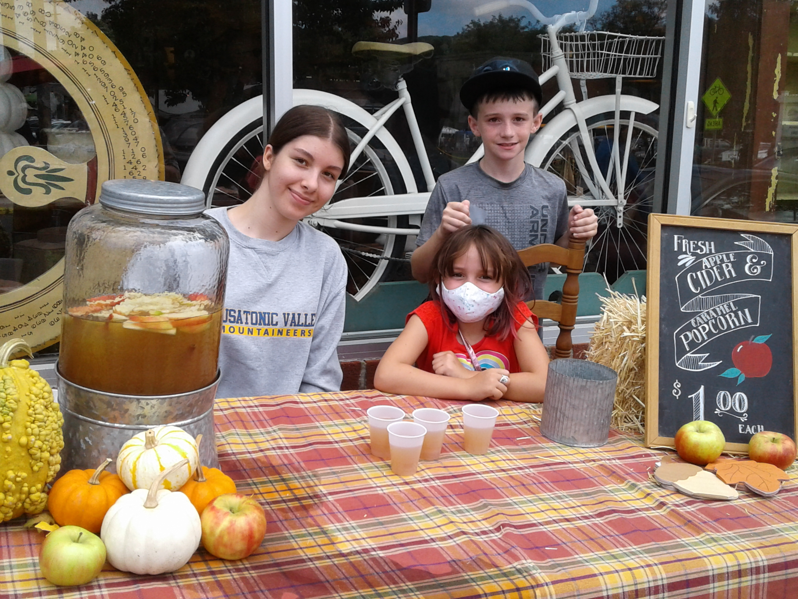 <strong>From left, Ella Hewing sold fresh apple cider in front of Merwin Farm &amp; Home with help from Natalie and Wyatt Merwin during the Millerton Food Festival. <em>Photo by Kaitlin Lyle</em></strong>