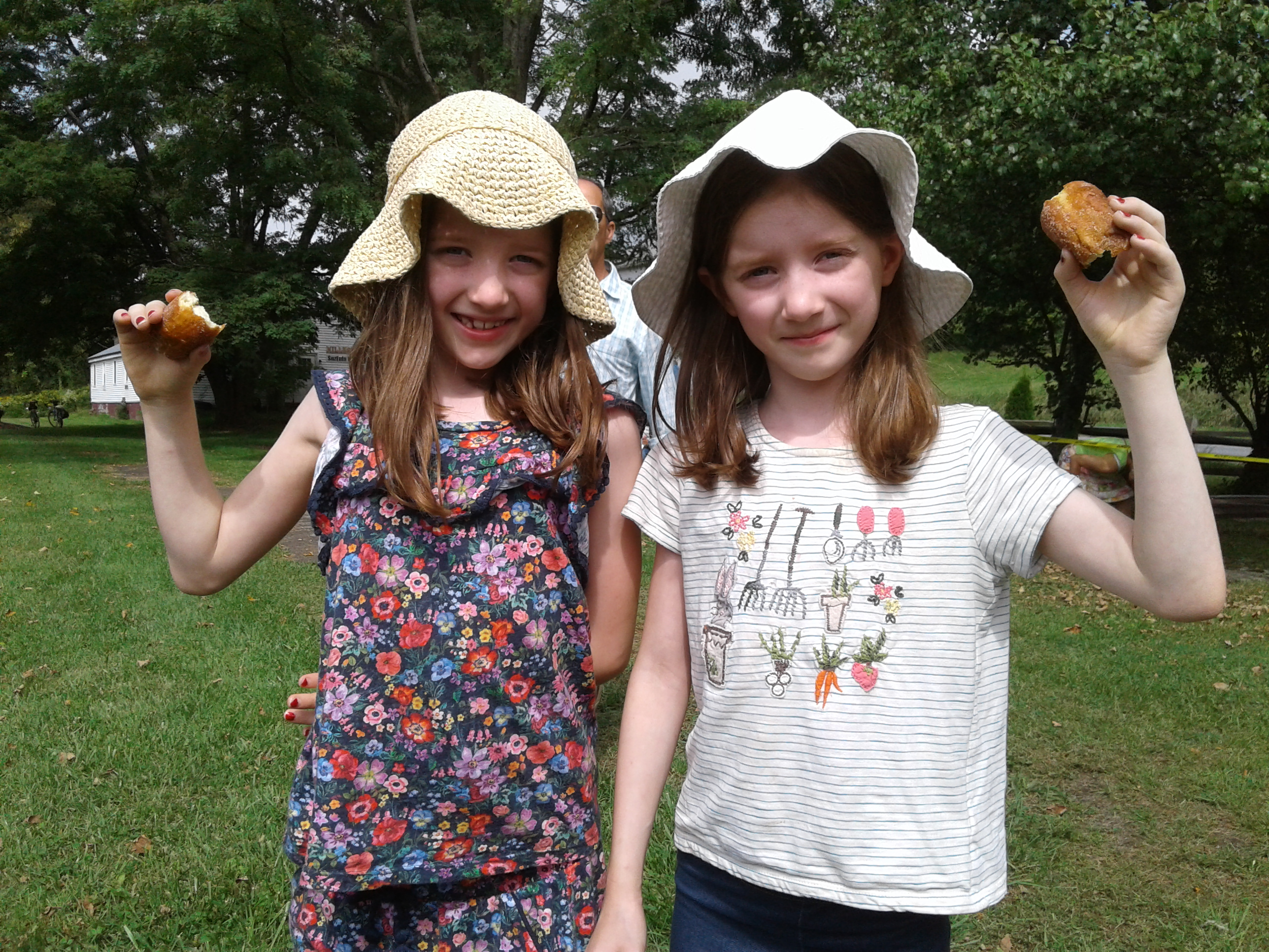 <strong>From left, twins Hazel and Clara Mork from Stanfordville split a doughnut purchased from the Cosmic Donuts tent on the Harlem Valley Rail Trail.<em>Photo by Kaitlin Lyle</em></strong>