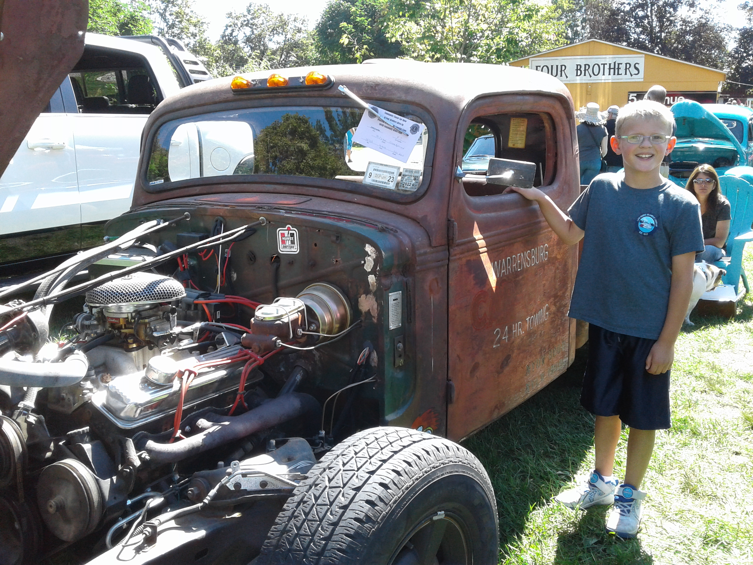 <strong>Visiting the Four Brothers Drive-In Theatre from Goshen, Conn., Jackson Magyar stopped to admire a 1939 Mack Rat Rod owned by Amenia Highway Superintendent Megan Chamberlin, pictured in the rear with her English bulldog, Bella.<em>Photoby Kaitlin Lyle</em></strong>