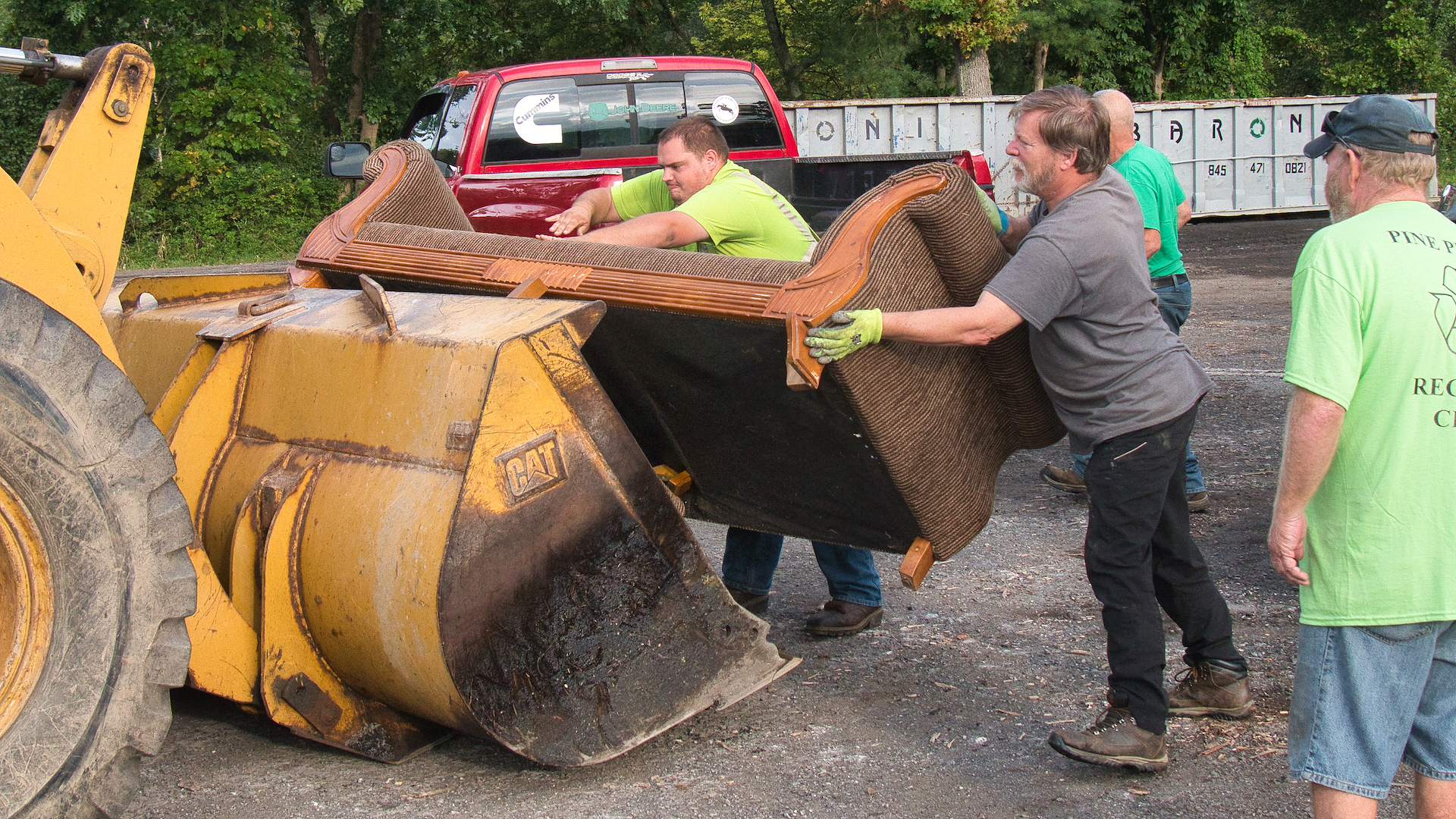 <strong>Volunteers and town representatives helping out at this year's Bob Couse Clean Up Day worked together to unload materials, such as this sofa, from residents' vehicles to be carted away. <em>Photo by Stan Hirson</em></strong>
