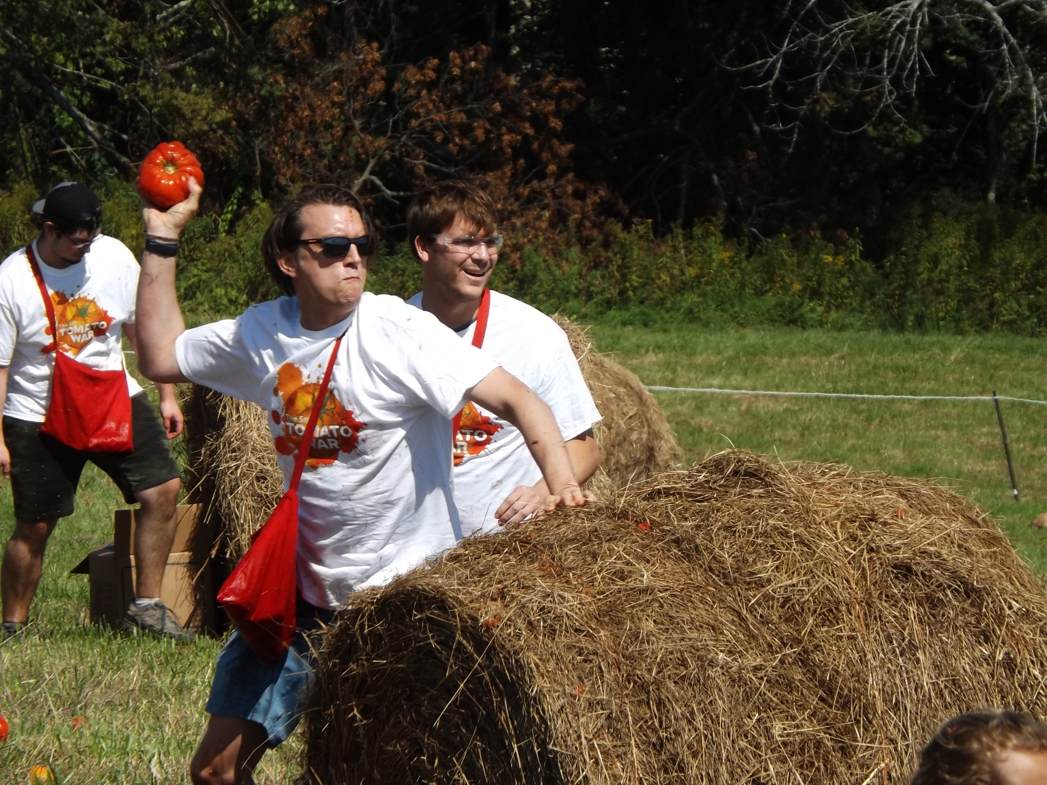 <strong>Grasping battered tomatoes in their hands, Tomato War participants popped up from behind hay bales to lob juicy red ammo at their opponents. <em>Photo by Kaitlin Lyle.</em></strong>