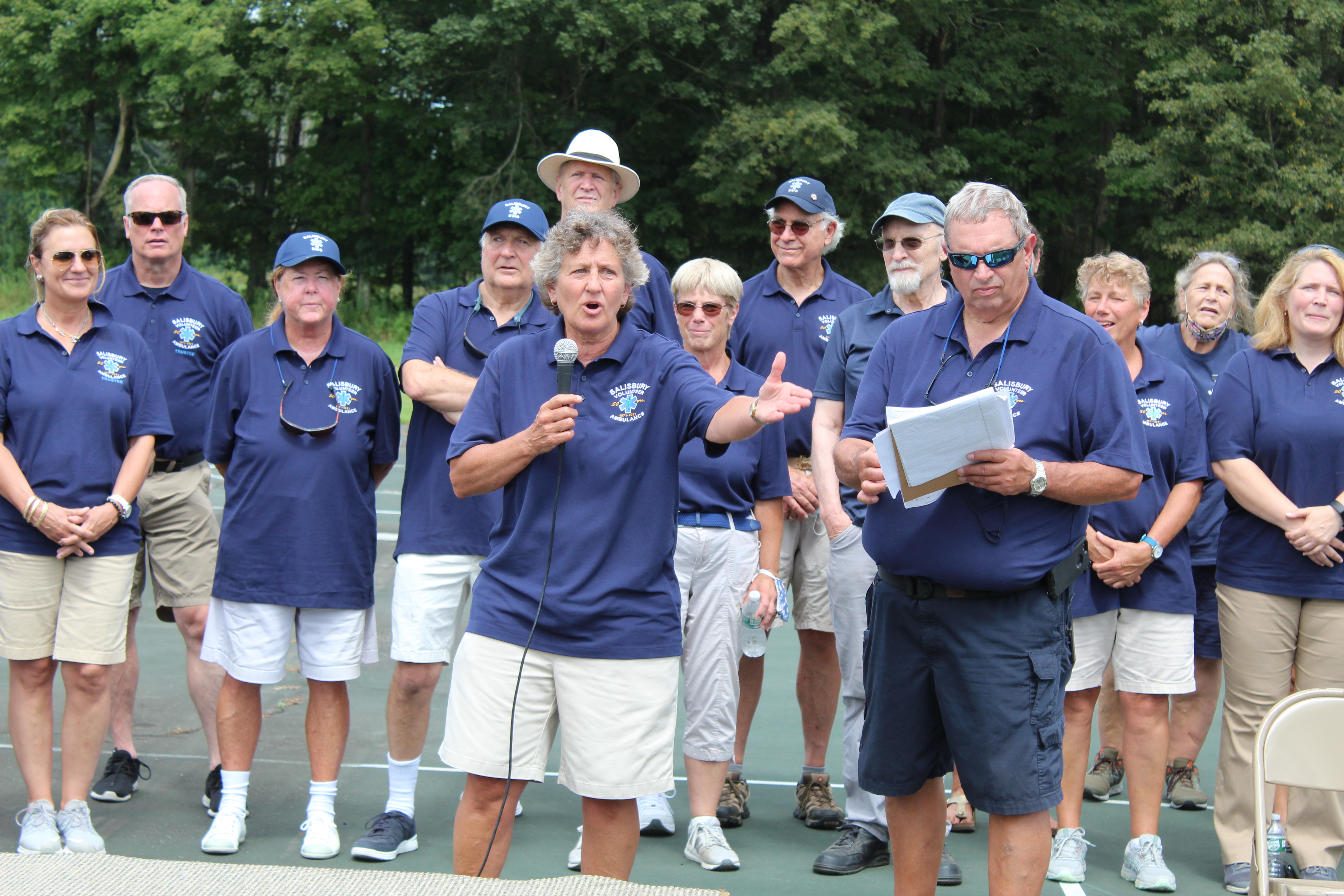 <strong>Mike Brenner, front right in photo, and Jacquie Rice, with microphone, invited all members and trustees, past and present, to come forward at the Salisbury Volunteer Ambulance Service 50th anniversary celebration at Trotta Field on Saturday, Aug. 21.</strong><em><strong>Photoby Patrick L. Sullivan</strong></em>