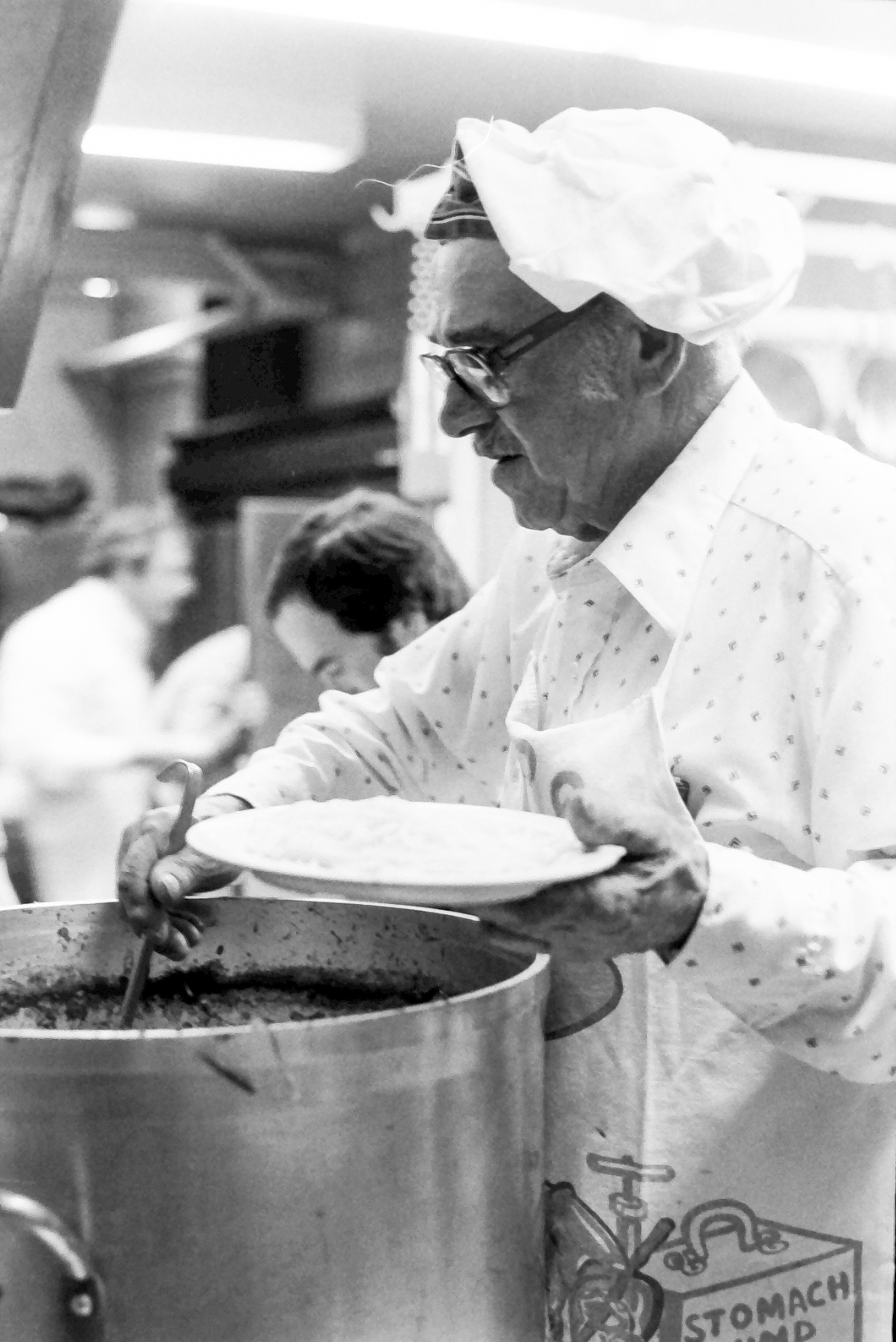"""This kind of fundraising supper is held several times every year in our area towns.This particular meal was at Sharon Center School, to raise funds for the Sharon Day Care Centet.The gentleman in the patterned shirt and entertaining apron is described in the Feb. 14, 1985, issue as """"Master spaghetti cook Fred Amerighi."""" If anyone recognizes someother volunteer chefs and kitchen workers, send a note to <a href=""""mailto:cynthiah@lakevillejournal.com"""">cynthiah@lakevillejournal.com</a>.<em><strong>Photo by Brigitte Ruthman</strong></em>"""