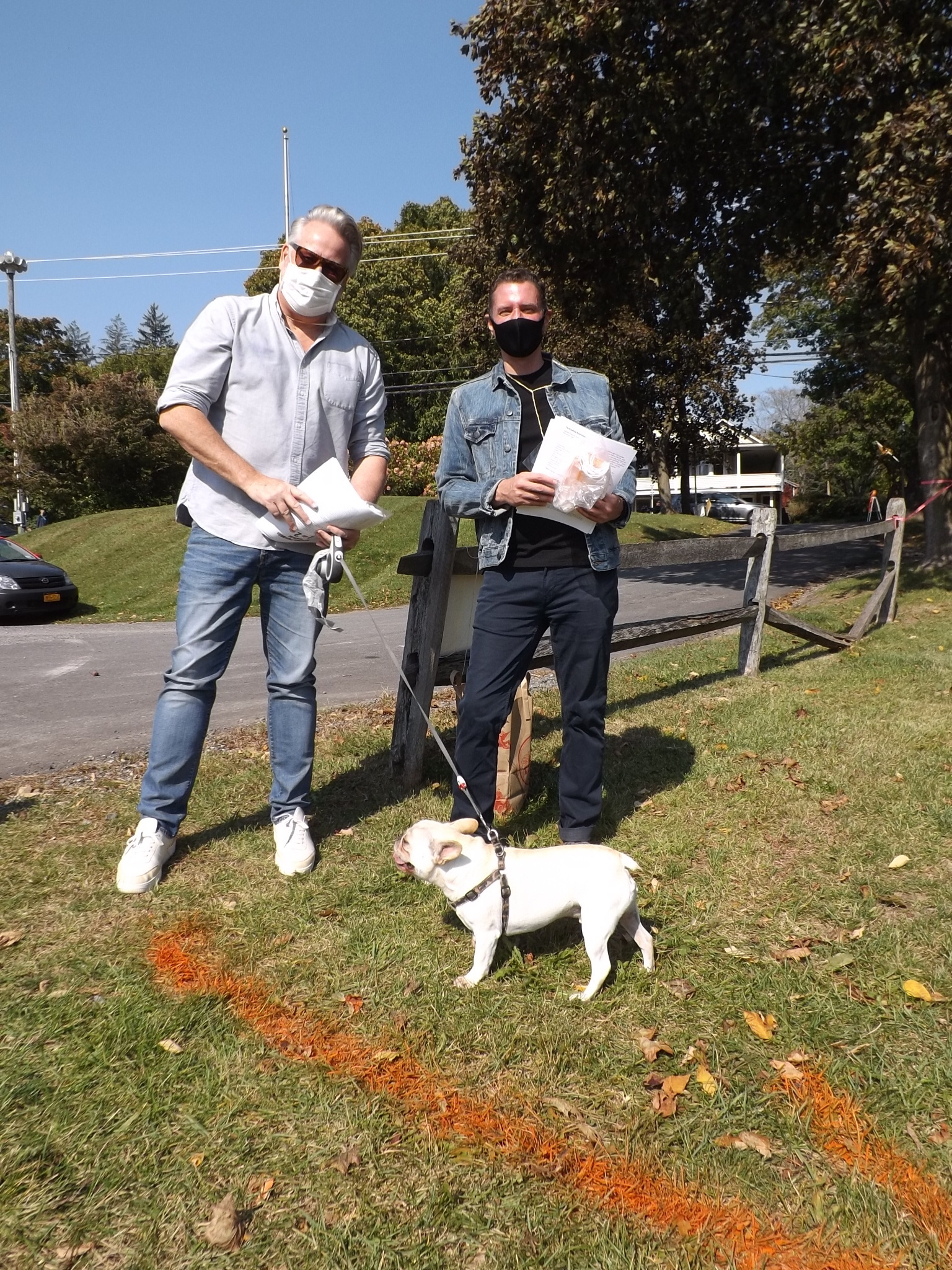 <strong>Leon Green, left, and Jason Durant welcomed visitors to the town of Hillsdale's Hamlet Park for the ninth annual Pumpkin Festival with help from Alfie, the French bull dog. <em>Photo by Kaitlin Lyle</em></strong>